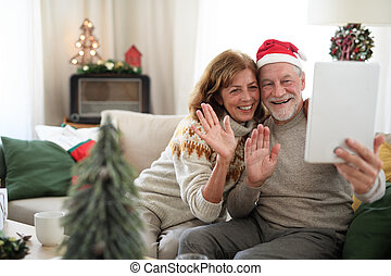 Front view of senior couple indoors at home at Christmas, taking selfie.