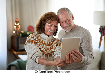 Front view of senior couple with tablet indoors at home at Christmas, taking selfie.