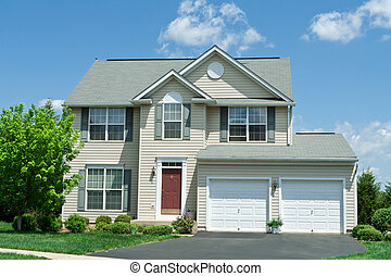 Modern vinyl sided single family home in suburban Maryland. House has two car garage, driveway and red door.