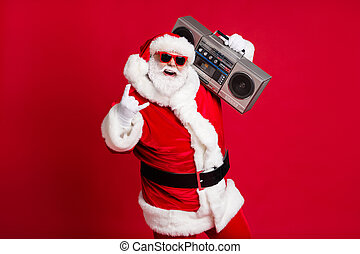 Full body size photo of retired old man grey beard hold boombox show horns make youngsters envious hard loud noise wear santa costume sunglass headwear x-mas isolated red color background