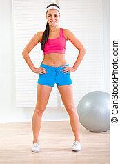 Full length portrait of girl in sportswear holding hand on hips