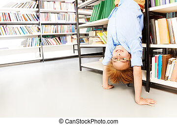 Funny boy standing on arms upside down