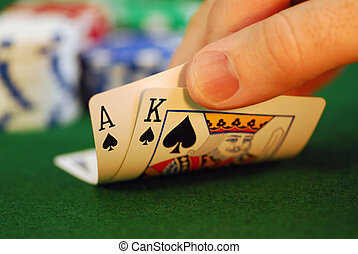 Man's hand lifting up playing cards at a poker table