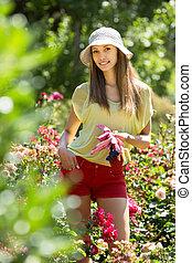 gardener standing near roses