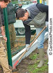 Gardeners putting up a perimeter