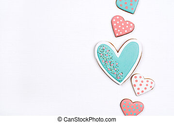 Gingerbread cookies with frosting in the shape of a heart on white background.