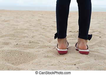 girl child standing face ocean beach sand