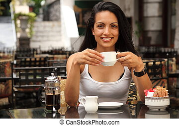 Attractive girl in bistro drinking a cup of coffee