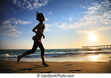 Girl running by the ocean at sunset