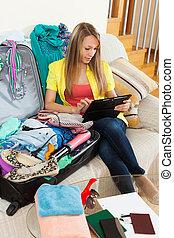 Girl sitting on sofa near luggage
