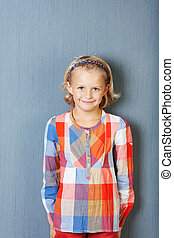 Girl Smiling While Standing Against Blue Wall