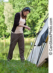 Girl trying to pitch a tent