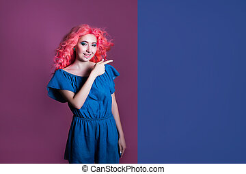 girl with pink hair in blue dress shows sign on lilac background, place for text