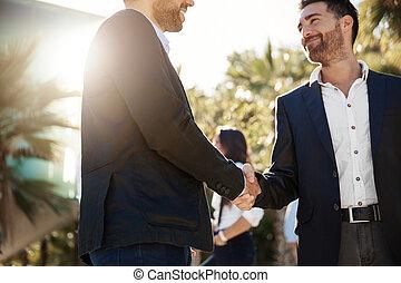 Glad businessman shaking hands with business partner