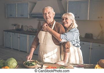 Glad wife hugging her husband in cook room