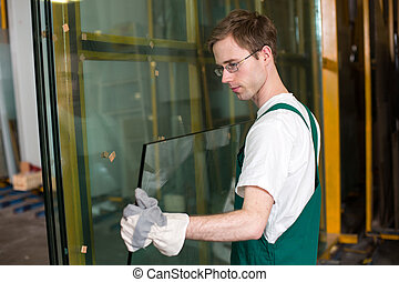 Worker in glazier's workshop, warehouse or storage handling glass