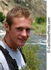 A handsome fisherman beside a mountain stream