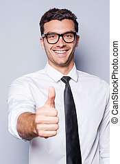 Good job! Happy young man in shirt and tie showing his thumb up and smiling while standing against grey background