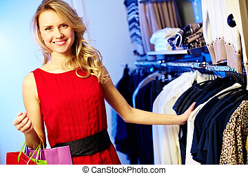 Portrait of pretty shopper looking at camera in clothing department