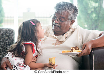 Granddaughter and grandfather eating cake