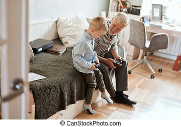 Grandfather and grandson playing video games on computer with joystick