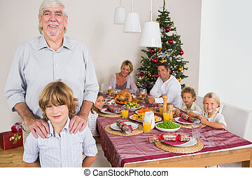 Grandfather and grandson standing beside the dinner table