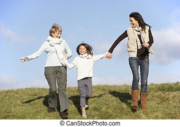 Grandmother And Mother Holding Hands With Young Girl