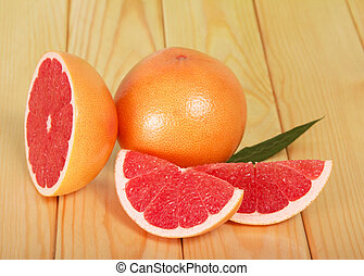 Grapefruit slices on background of wooden table
