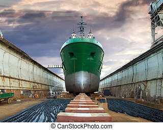 The ship in dry dock during the overhaul, under dramatic sky.