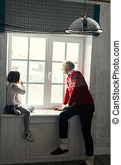 grey-haired man and a little girl are looking at the window