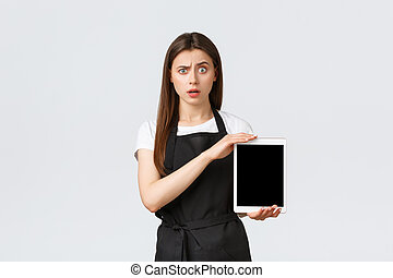 Grocery store employees, small business and coffee shops concept. Confused and puzzled cute girl barista in black apron raise eyebrow shocked and showing digital tablet screen