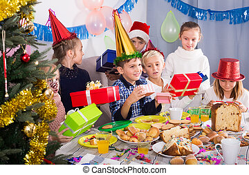 Group of children exchanging Christmas gifts