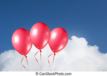group of festive red balloons on blue sky clouds background