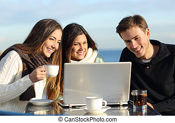 Group of friends watching a laptop in a restaurant