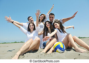 Group of happy young people in circle at beach have fun