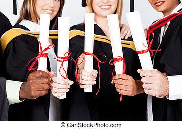 multiracial graduates holding certificates