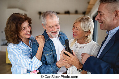 Group of senior friends at dinner party at home, greeting.