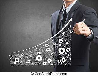 Business man drawing growing economy and industry represented by gears as a symbol of industrial activity