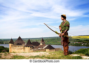 Medieval archer with bow and arrows on fortress background