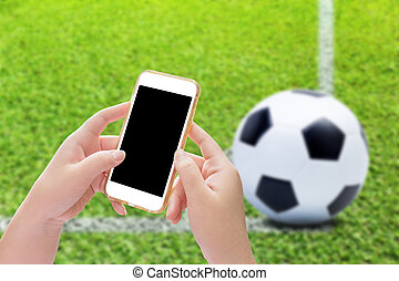 Hand holding smartphone with soccer ball on play fields