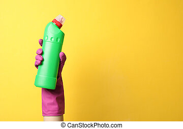 Hand in cleaning glove hold bottle with detergent on yellow background, space for text