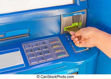 Hand insert credit card to ATM bank cash machine for withdraw money