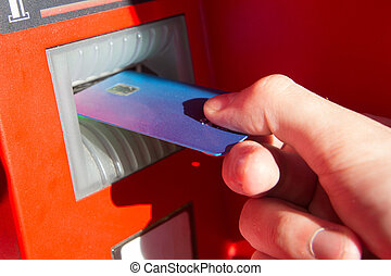Hand of a man with a credit card, using an ATM.
