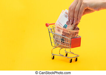 Hand puts another five thousandth bill in a grocery basket