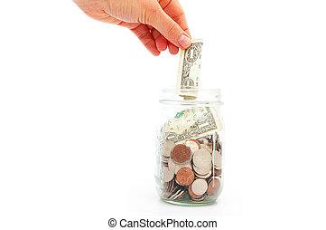 hand putting a dollar in a coin jar