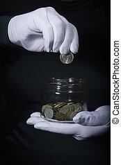 Hand throws a coin in a jar