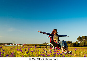 Happy handicapped woman on a wheelchair over a green meadow