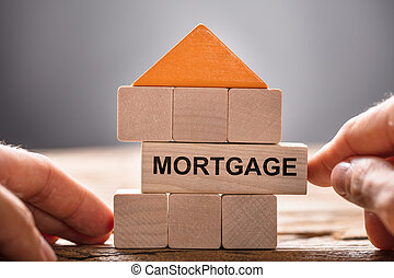 Hands Building House Model With Mortgage Block