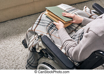 Hands of young disable woman in wheelchair holding book on her knees