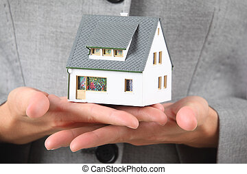 hands with model of house